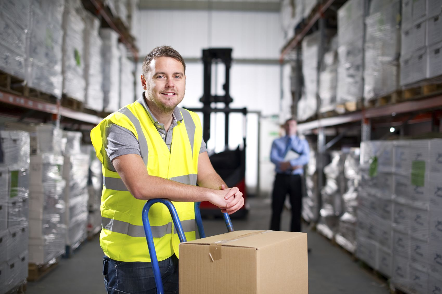 Warehouse worker stands with a hand truck carrying boxes as his manager looks on in the background