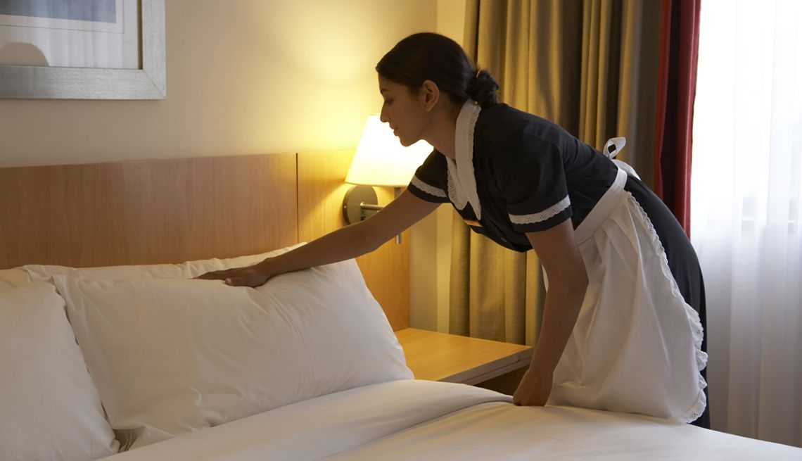 Chamber maid working in hotel bedroom. housekeeper